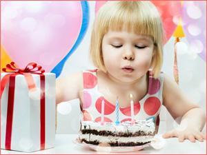 Ребенок задувает свечки на вкусном торте для дня рождения